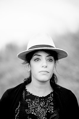 Portrait of black-haired woman with straw hat - p552m2287964 by Leander Hopf