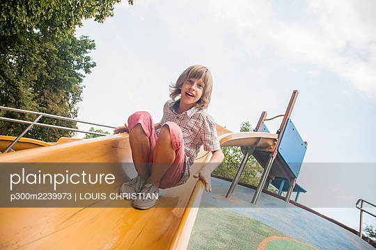 Boy playing on slide against sky at park - p300m2239973 by LOUIS CHRISTIAN