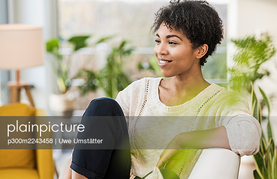Smiling woman looking away while sitting on sofa at home - p300m2243458 by Uwe Umstätter