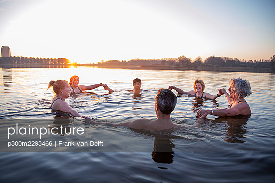 Male and female friends holding hands in water - p300m2293466 by Frank van Delft