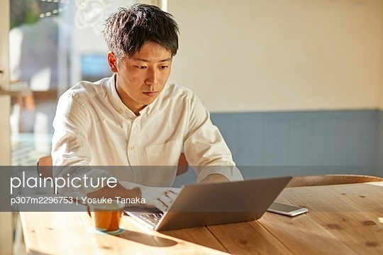 Young Japanese man at a cafe - p307m2296753 by Yosuke Tanaka