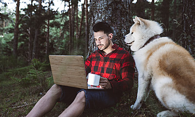 Male hiker with coffee cup using laptop while sitting by dog in forest - p300m2293537 by Jose Carlos Ichiro