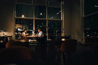 Male and female entrepreneurs working late in dark office at night - p426m2194736 by Maskot