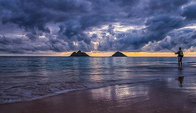 Man fishing in the ocean at Lanikai Beach; Waikiki, Oahu, Hawaii, United States of America - p442m2077629 by Robert Postma