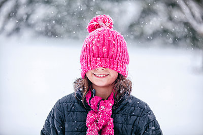 Girl with pink knitted hat pulled over eyes - p924m1224519 by Rebecca Nelson