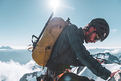 Climber looking at phone on Tantalus Traverse, close to Squamish, British Columbia, Canada - p924m2271172 by Alex Eggermont