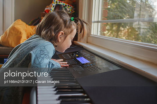a little girl curiously explores the keys on a piano keyboard - p1166m2131317 by Cavan Images