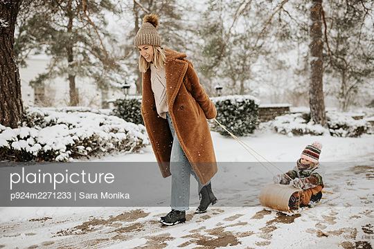 Canada, Ontario, Mother pulling daughter (2-3) on toboggan - p924m2271233 by Sara Monika