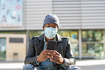 young african man in the city sending a message from his smartphone - p1166m2218248 by Cavan Images