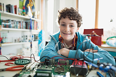 Portrait confident boy assembling circuit board in bedroom - p1192m1129534f by Hero Images