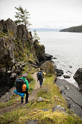 Active senior couple backpacking on cliff trail overlooking ocean - p1192m2000410 by Hero Images