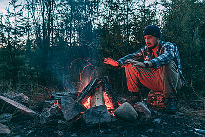 Man sitting at campfire in rural landscape - p300m1537443 by Vasily Pindyurin