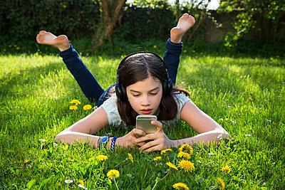Girl lying on meadow listening music with headphones using smartphone - p300m1587666 von Larissa Veronesi