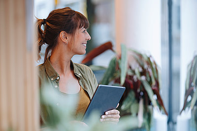 Female entrepreneur looking away while holding digital tablet standing in coffee shop - p300m2226422 by Gustafsson
