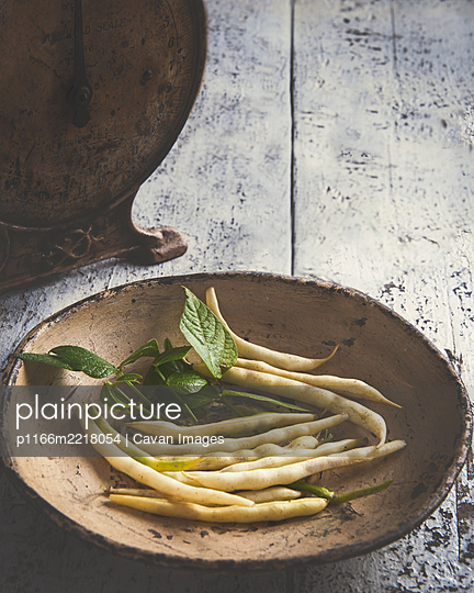 shappy high angle of french wax beans, plate placed on wooden table - p1166m2218054 by Cavan Images