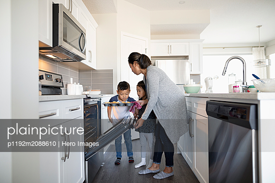 Mother and children baking cupcakes in kitchen - p1192m2088610 by Hero Images