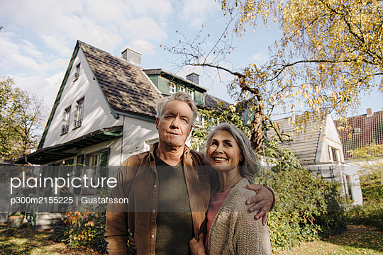 Senior couple in garden of their home in autumn - p300m2155225 by Gustafsson