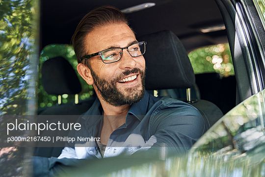 Portrait of smiling man sitting in car - p300m2167450 by Philipp Nemenz