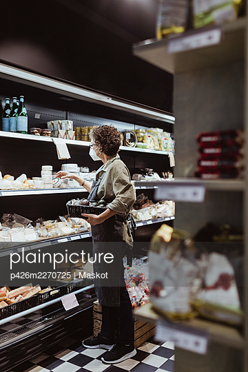 Female owner arranging food product on rack at deli shop during pandemic - p426m2270725 by Maskot