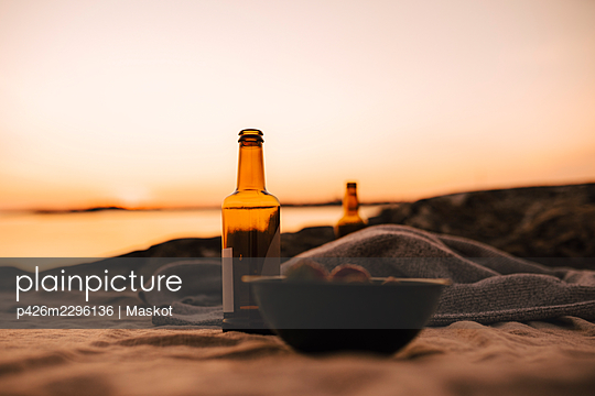 Food bowl and beer bottle at lakeshore during sunset - p426m2296136 by Maskot
