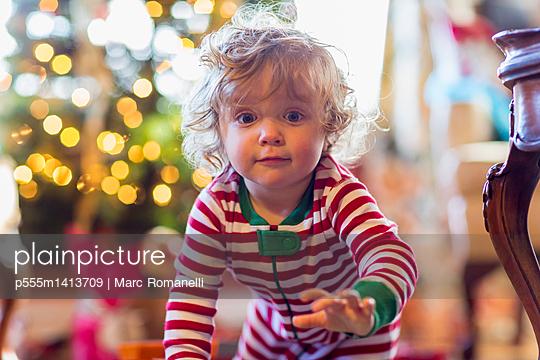 Caucasian baby boy crawling near Christmas tree