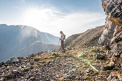 A young woman trail runner takes a break high up on Arapaho Pass - p1166m2130619 by Cavan Images