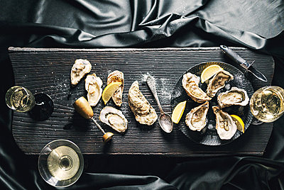 Open oysters with lemon and wine in a black plate, top view - p1166m2151995 by Cavan Images