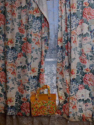 Floral patterned curtain and orange coloured bag - p1279m1564424 by Ulrike Piringer