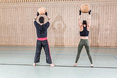 Man and woman practising with medicine balls in sports hall - p300m2144540 von Stefanie Baum