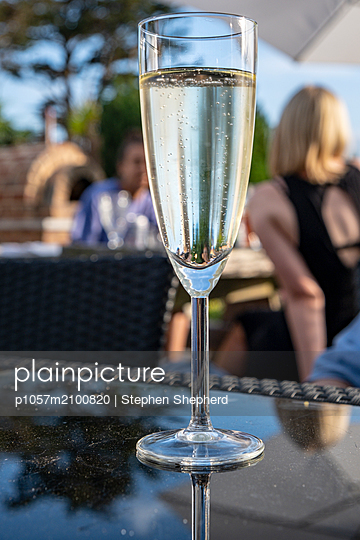A flute glass of sparkling wine backlit by the setting sun covered in condensation from the cold liquid inside with a small group of people sitting in the background in the summer sunshine. - p1057m2100820 by Stephen Shepherd