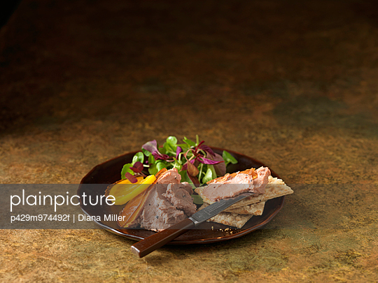 Christmas snack of duck liver pate with truffles. Mixed salad leaves and orange slices - p429m974492f by Diana Miller