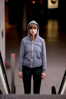 Junge Frau mit Kapuzenjacke oben an Rolltreppe im Bahnhof - p1212m1137058 von harry + lidy