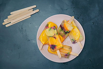 Homemade orange and lemon popsicles with edible flowers on plate - p300m1581130 von skabarcat