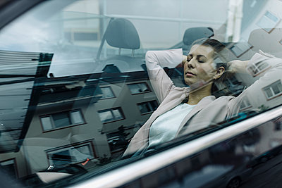 Businesswoman relaxing in car - p300m2242604 by Gustafsson