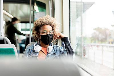 Woman wearing mask looking through window while traveling in tram - p300m2276395 by Rafael Fernandez Torres