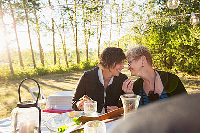 Mom and daughter sharing a laugh at outdoor dinner. - p328m784046f by Hero Images