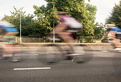 Three cyclists speeding on urban road in racing cycle race - p429m1118555f by Seb Oliver