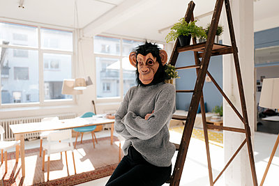 Young woman with monkey mask in her apartment - p586m2021369 by Kniel Synnatzschke