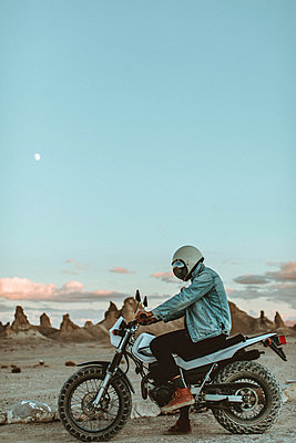 Motorcyclist on stationary bike, Trona Pinnacles, California, US - p924m2068332 by Peter Amend