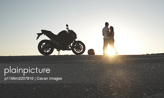 backlighting of a couple posing on the road with their motorcycle - p1166m2207816 by Cavan Images