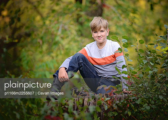 Young Blond Boy Sitting Outside in the Trees - p1166m2255607 by Cavan Images