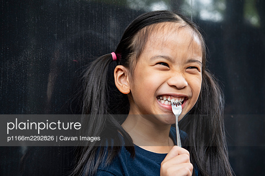young Thai girl biting on fork - p1166m2292826 by Cavan Images