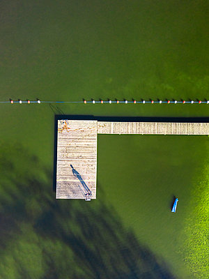 Aerial view of man standing on jetty at a lake - p300m1505895 by Stefan Schurr