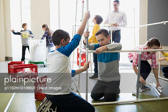Students assembling model pipeline in science center - p1192m1019862f by Hero Images