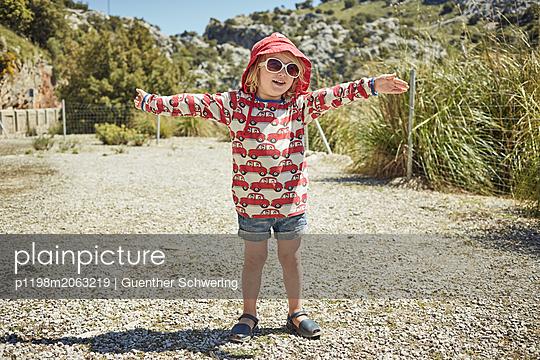 Kind mit Sonnenhut breitet seine Arme aus - p1198m2063219 von Guenther Schwering