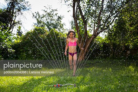 Little girl having fun with lawn sprinkler in the garden - p300m2004398 von Larissa Veronesi