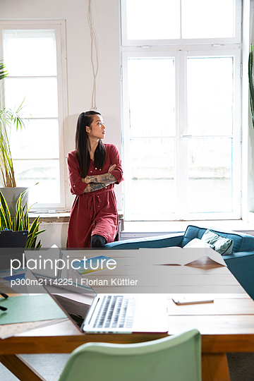 Woman looking out of window in office - p300m2114225 by Florian Küttler
