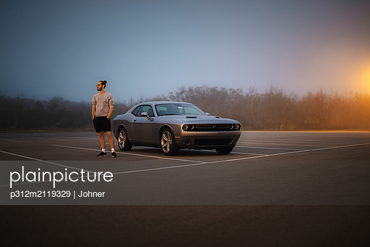 Man standing near vintage car - p312m2119329 by Johner