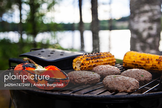 Corn, bell pepper and meat being grilled on barbecue - p426m747246f by Anders Bergstedt