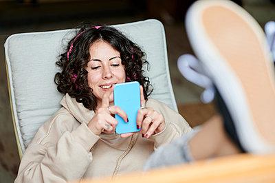 Spain, Andalucia, Jerez, woman with headphones using mobile phone at home. - p300m2282288 von Kiko Jimenez